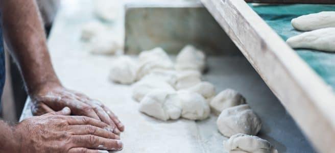 Bakery hands knead bread.